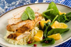 Dietetyczna  pierś z kurczaka podana na ryżu z sałatką ze szpinaku